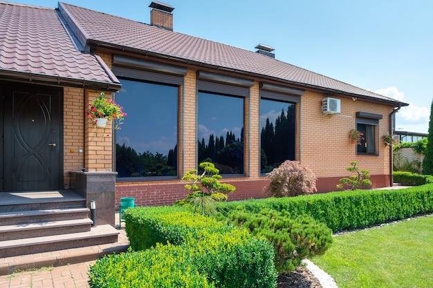 Villa im europäischen stil mit und garten mit schön geschnittenen büschen vor dem haus. landschaftsdesign. foto in hoher qualität