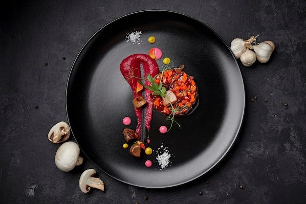 Vinaigrette-salat auf einem schwarzen hintergrund, mit pilzen und knoblauch