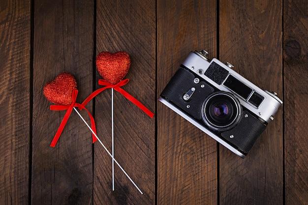 Vintage alte kamera mit herzen auf rustikalem holztisch. draufsicht