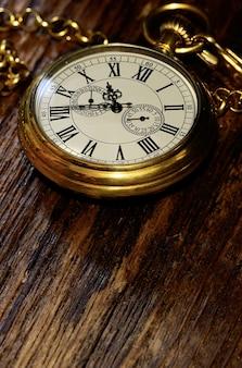 Vintage alte taschenuhr auf verwittertem holzhintergrund