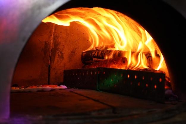 Vintage alter ofen mit feuer innen zum backen der ursprünglichen pizza.