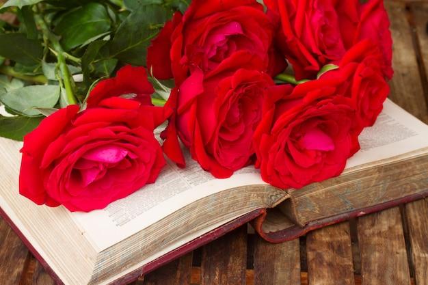 Vintage altes offenes buch auf tisch mit roten rosen