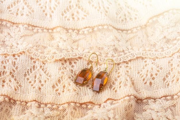 Vintage antike ohrringe, ohrentropfen aus citrin auf zartem elfenbeinfarbenem spitzentuch