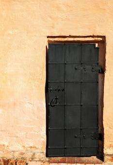 Vintage antike schwarze eisentür auf gelbem hintergrund
