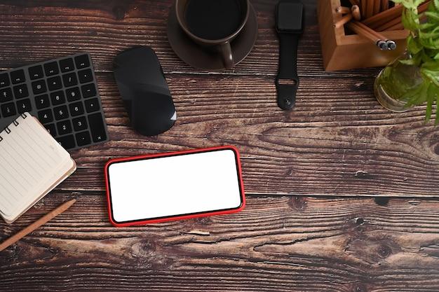 Vintage-arbeitsplatz mit smartphone, notebook, smartwatch, zimmerpflanze und kaffeetasse auf holztisch.