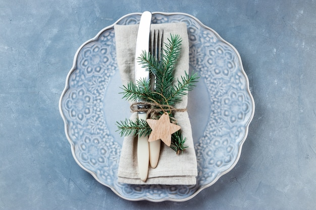 Vintage besteck auf leinenserviette und leerem teller - weihnachtseinstellung in blautönen.