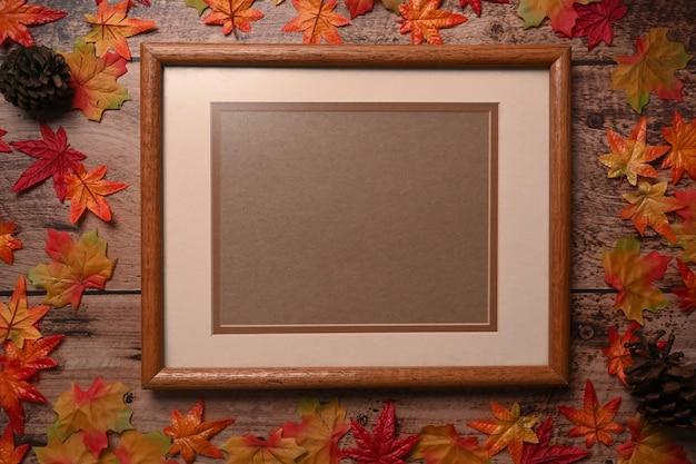 Vintage bilderrahmen mit herbstahornblättern und tannenzapfen auf holzuntergrund.