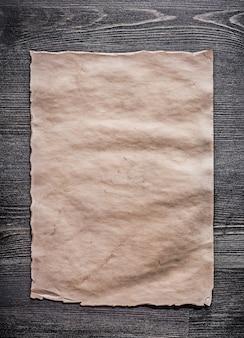 Vintage blatt papier auf holzbrett vertikale ansicht