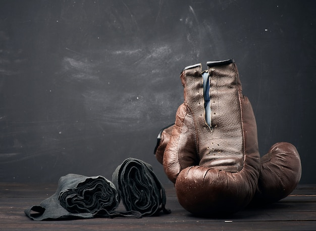 Vintage boxhandschuhe aus braunem leder und schwarzer elastischer verband für die hände