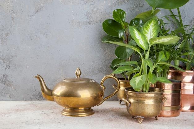 Vintage bronze teekanne und grünpflanzen