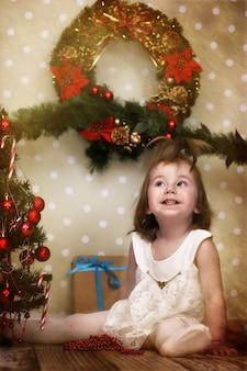 Vintage-effekt auf foto süßes kleines mädchen verkleidet weihnachtsbaum auf dem boden im zimmer