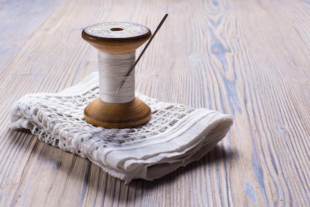 Vintage fadenspule auf holztisch, handwerksthema.