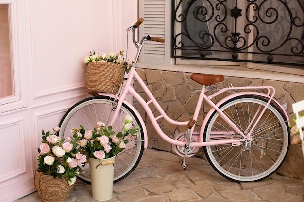 Vintage fahrrad mit korb mit blumenstrauß blumen von rosen steht in der nähe von café