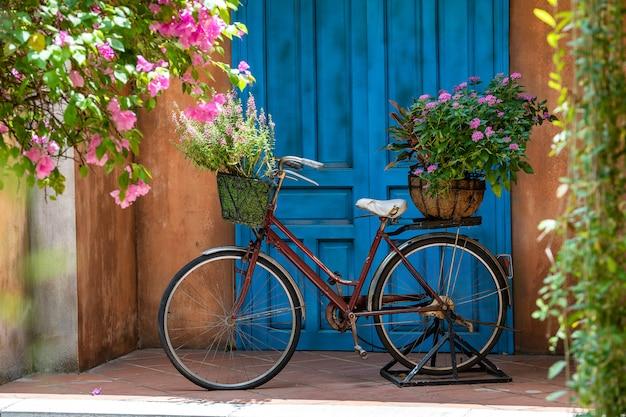 Vintage fahrrad mit korb voller blumen neben einem alten gebäude in danang, vietnam, nahaufnahme