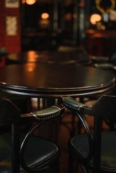 Vintage fasstisch mit zwei vintage hochstühlen, dunklem interieur und dunklen möbeln.