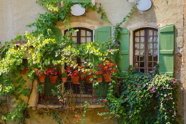 Vintage-fenster mit blumen aus holz grüne fensterläden weiße vorhänge im alten haus des französischen dorfes