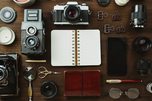 Vintage filmkamera, objektive und briefpapier auf dunklem holztisch