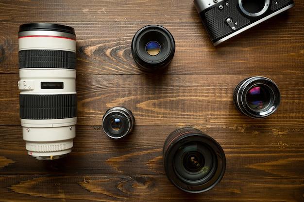 Vintage filmkamera und verschiedene objektive, die auf holzhintergrund liegen