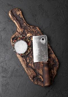 Vintage fleischmesser beil auf vintage schneidebrett und schwarzen stein