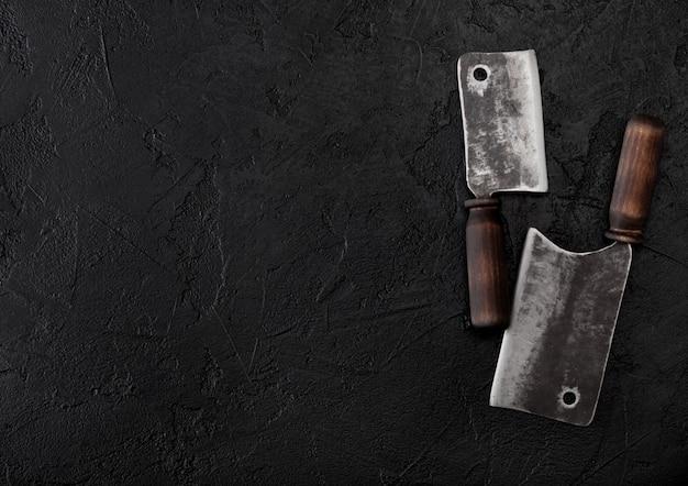 Vintage fleischmesser beile auf schwarzem steintisch.