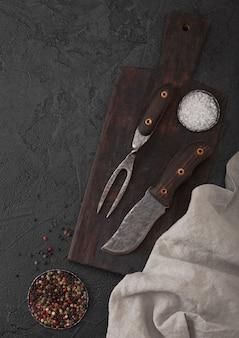 Vintage fleischmesser und gabel auf vintage schneidebrett und schwarzem stein