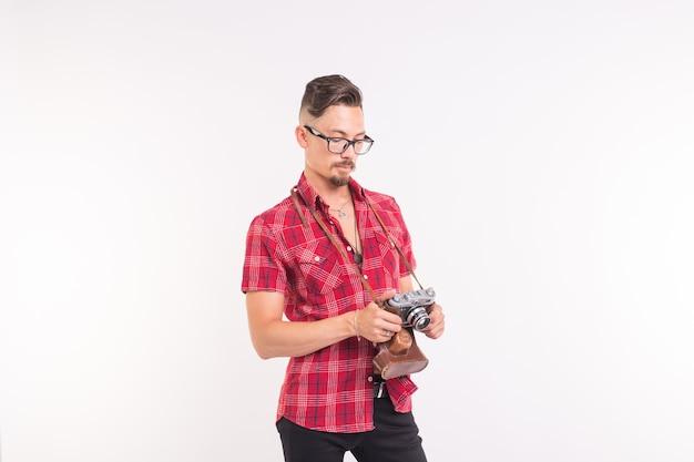 Vintage, fotograf und people-konzept - gut aussehender mann mit retro-kamera auf weißem hintergrund mit kopienraum.