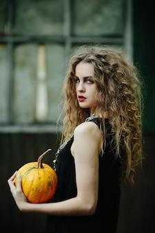 Vintage frau als hexe, posiert vor dem hintergrund eines verlassenen ortes am vorabend von halloween