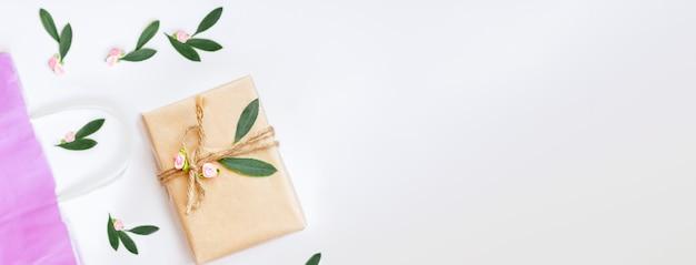 Vintage geschenkverpackung in rosa öko-papier auf weißem hintergrund. geschenk mit rosenblüten verziert. geburtstag, mutter, valentinstag, frauen, hochzeitstag konzept, draufsicht, flach. Premium Fotos