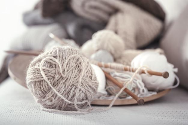 Vintage holzspeichen und -fäden zum stricken in form eines herzens auf einem holzteller. stillleben foto