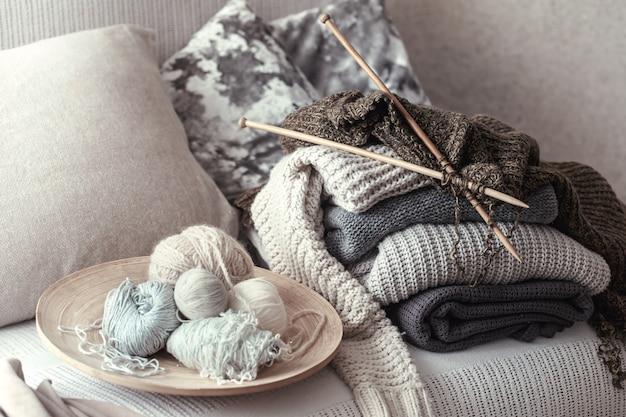 Vintage holzstricknadeln und -fäden zum stricken auf einem gemütlichen sofa mit kissen und pullovern
