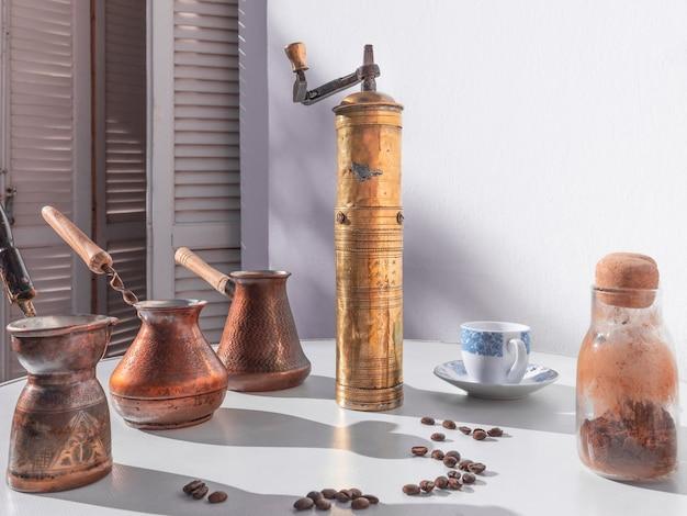 Vintage kaffeemühle steht vor drei cezves kaffeetasse und glasflasche mit gemahlenem kaffee