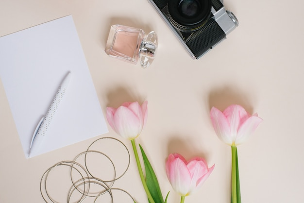 Vintage-kamera-rosa-frühlingstulpen-notizbücher ein leeres blatt papier und ein stiftparfüm