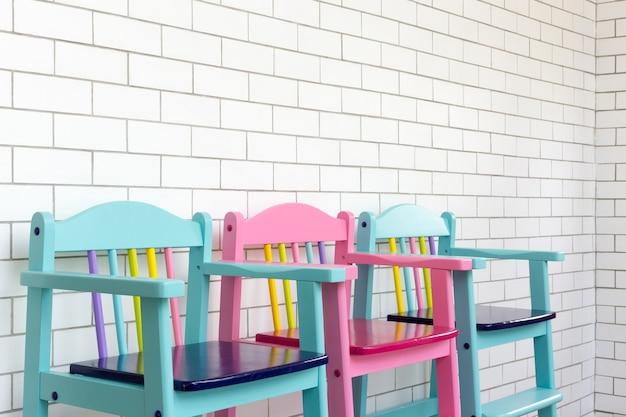 Vintage kindstühle auf weißer backsteinmauer