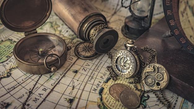 Vintage kompass, uhr anhänger und teleskop auf alte weltkarte