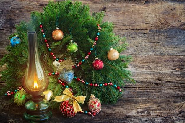Vintage leuchtende laterne mit verziertem immergrünem weihnachtskranz auf holz