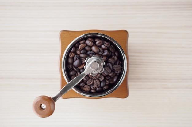 Vintage manuelle kaffeemühle mit gerösteten kaffeebohnen