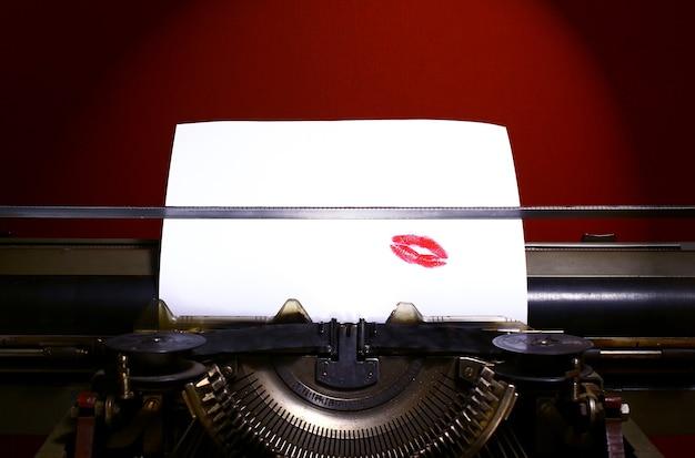 Vintage manuelle schreibmaschine. roter lippenstiftdruck auf papier.