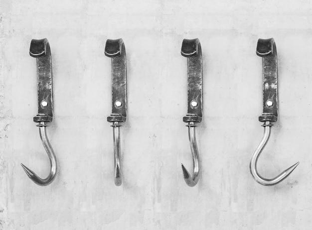 Vintage metallhaken für heu oder fleisch an einer betonwand befestigt