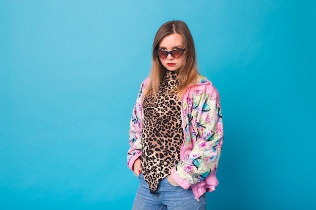 Vintage mode-look-konzept - hübsche junge frau, die eine retro-rosa jacke und leopardenkörper auf blauer wand mit kopienraum trägt