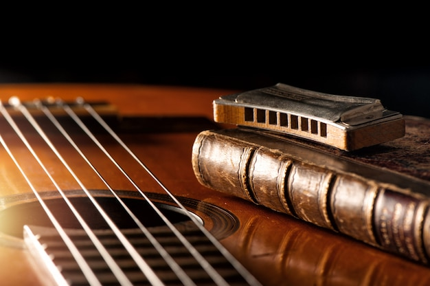 Vintage mundharmonika auf akustikgitarre