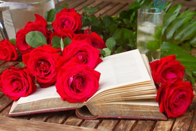 Vintage offenes buch auf tisch mit roten rosen