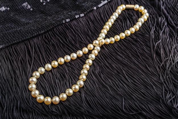 Vintage perlenschmuck auf kleinen schwarzen kleid. gatsby oder chicago fashion look. luxus weiße halskette. immer bereit für die party. elegantes geschenk für frau.