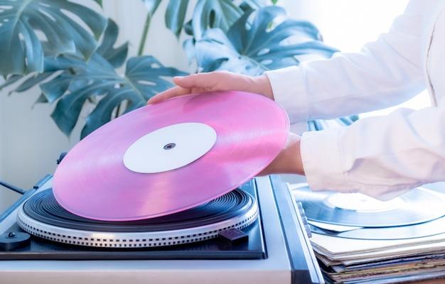 Vintage plattenspieler rosa vinyl plattenhand tropischen blätter alten plattenspieler