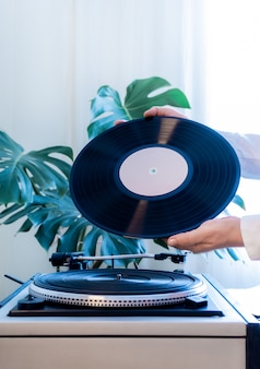 Vintage plattenspieler vinyl plattenhand tropische blätter alten plattenspieler