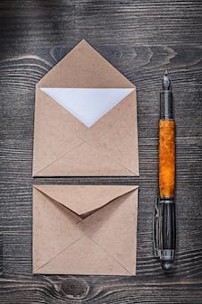 Vintage postumschläge brief füllfederhalter auf holzbrett
