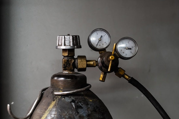 Vintage propangastank mit druckmessern. nahaufnahmebild des komprimierten zylinders mit flüssigem gas zum schweißen