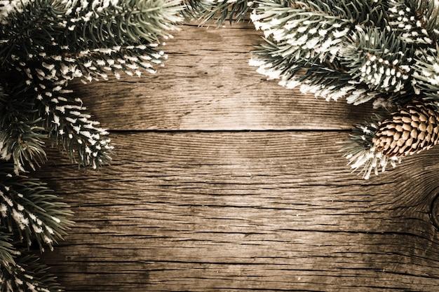 Vintage-rahmen aus zweig des weihnachtsbaums auf altem holz