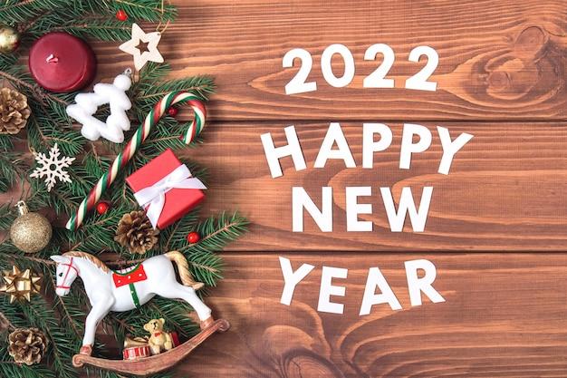 Vintage-rahmen mit text guten rutsch ins neue jahr 2022. tannenzweige mit zapfen, süßigkeiten, roten und goldenen weihnachtskugeln auf dunklem holzhintergrund. retro-postkartenmodell. flach liegen.