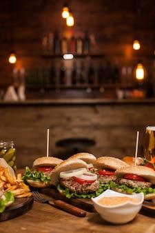 Vintage restauranttisch voller köstlicher burger. weiße zwiebeln. frisch gegrilltes fleisch.