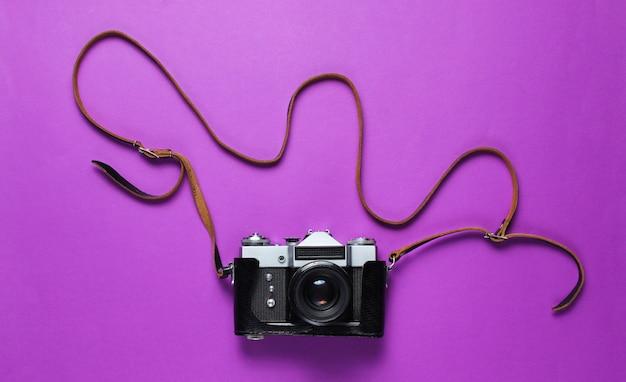 Vintage retro-filmkamera im lederbezug mit riemen auf lila.
